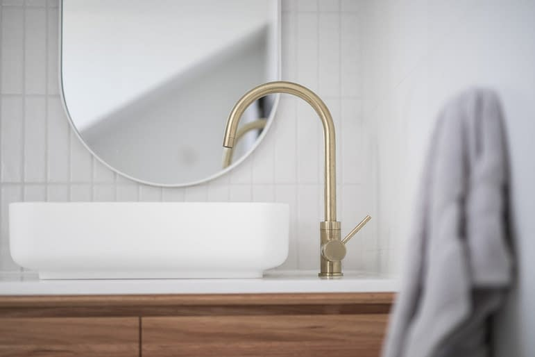 brushed-brass-tap-mixer-on-timber-vanity-with-white-basin-bowl-against-white-tiled-wall-in-a-new