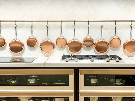 Row of gleaming copper pans hanging on the wall in luxury kitchen